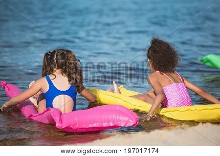 back view of little girls in swimsuits on inflatable mattresses at sea