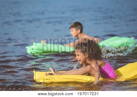 side view of happy african american girl swimming on inflatable mattress at sea