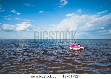 little boy swimming on colorful inflatable doughnut at sea