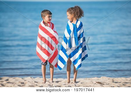 Multicultural Children In Towels Looking At Each Other While Standing At Seaside