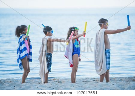 Multicultural Kids In Swimming Masks With Water Toys In Hands On Beach