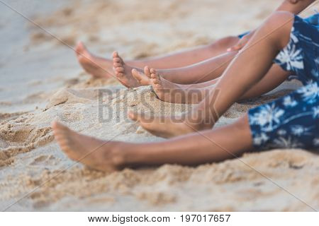 Cropped Shot Of Children Lying Together On Beach