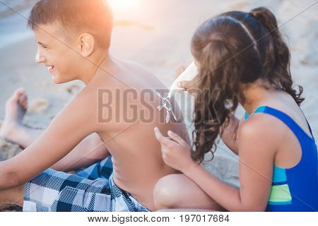 Side View Of Little Girl Applying Sun Cream On Boy On Beach