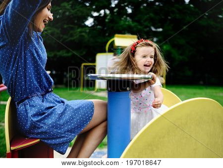 Young mother plays in the playground with the little daughter. Woman and charming girlie turning on the carousel. Serene summer day. Good mood.