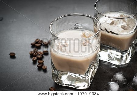Coffee liqueur in glasses with ice and coffee beans on black table. Close up.