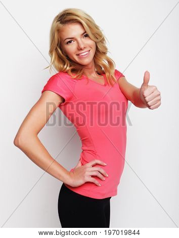 blonde very happy fitness woman showing thumb up on white background
