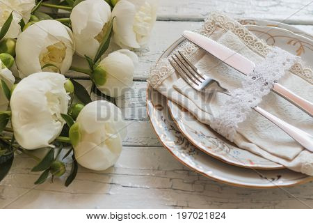 Tableware And Silverware With A Bouquet Of White Peonies On The Old White Wooden Boards