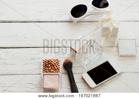 Rouge, Brush, Sunglasses, Phone And A Bottle Of Perfume On The Wooden Table