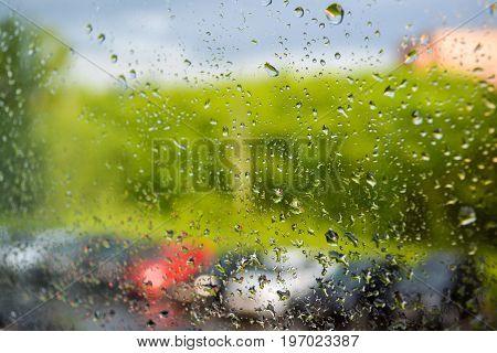 Rain drops on the window. A row of blurry cars outside the window. Summer rain on a sunny day.
