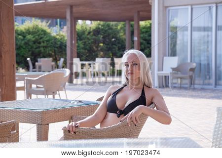 blonde girl sitting at the beach restaurant