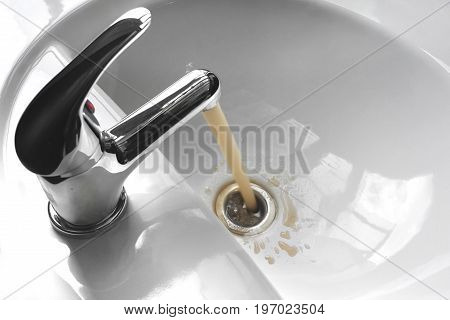 Water tap faucet with flowing contaminated muddy and dirty water in a white bathroom sink.