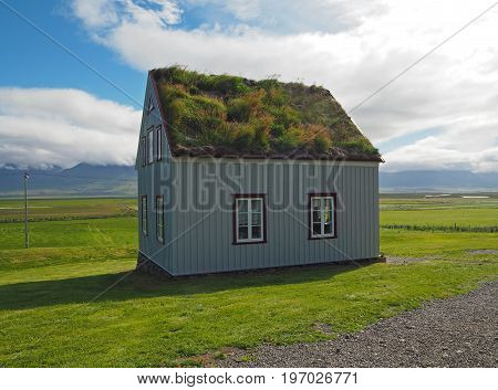 Glaumber - open-air folk museum - tradicional icelandic house with turf roof and white red windows with green grass and blue sky