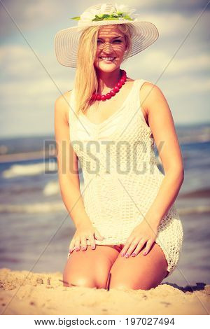 Summer time people concept. Attractive lady sitting on the sand. Woman has nice white dress and hat.