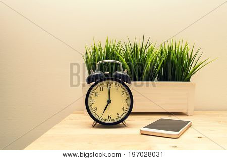 mobile smartphone, black vintage alarm clock times at 7 o'clock morning and green tree in silver pot small home decorative on wooden table and white wall,  vintage tone retro style