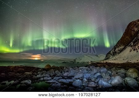 The beautiful shapes of Aurora Borealis, Northern Lights, in Tromso, Norway in front of Norwegian fjord during the winter season.