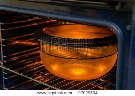 Closeup image of plastic bowl inside working modern oven