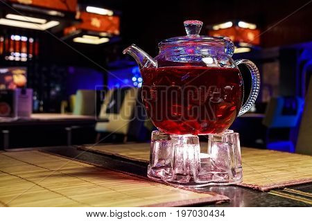 Closeup glass teapot with red fruit tea inside
