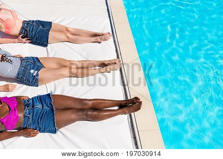 Crooped image of young women lying near swimming pool at resort