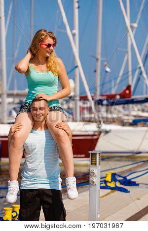 Relationship goals summer love concept. Man giving girlfriend piggyback ride on marina.