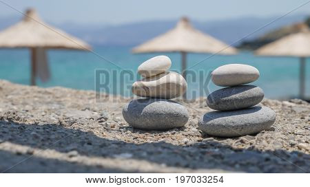 Two pebble towers with sun umbrellas on a sea shore