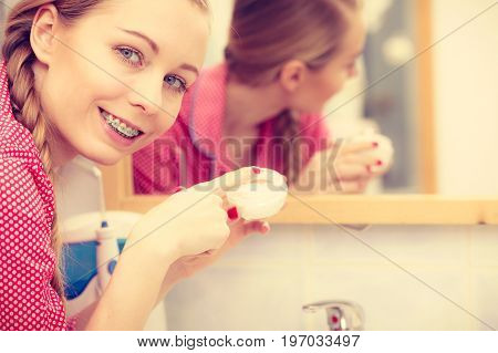 Young blonde woman applying moisturizing skin cream on face looking in bathroom mirror. Girl taking care of dry complexion layering moisturizer. Skincare treatment