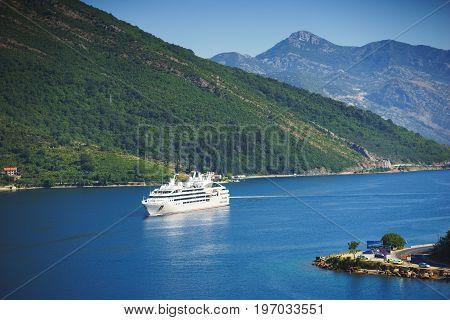 White passenger liner in the bay. Montenegro, Boka Kotorska bay on a hot summer day. Travel on a cruise liner to Montenegro.