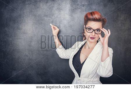 Serious Teacher In Glasses On The Blackboard Background