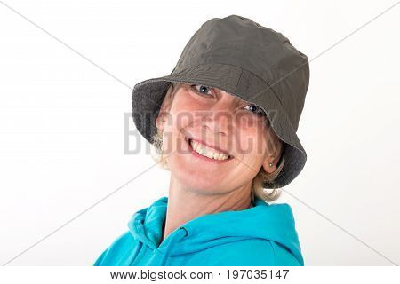 Beautiful european mid aged woman with blonde hair dressed in a light blue casual hooded jacket wearing a khaki hat - studio shot in front of a white background.
