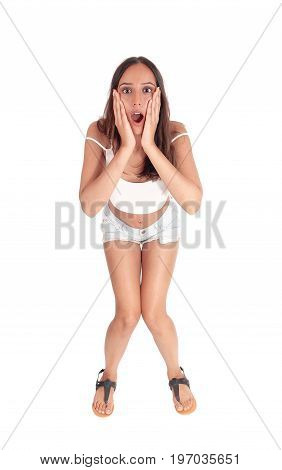 A young screaming woman standing bend forwards with her hands on her face yelling isolated for white background