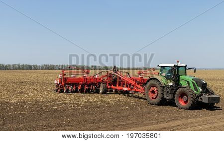 Dykanka UKRAINE - APRIL 30 2017: Farmer tractor working the field. Farm machines are preparing a field for sowing in the spring season