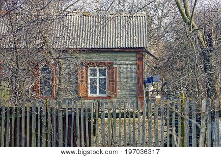 Old house made of wood with a slate roof behind a wooden fence
