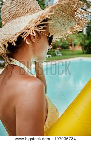 Summer holiday fashion concept - suntanned young woman relaxing near swimming pool,Wearing wide brimmed hat with stripes, stylish high waist swimsuit.