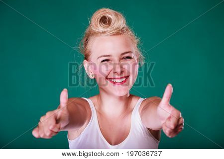 Symbols gestures concept. Smiling young woman with pinup hair making thumbs up gesture. Studio shot on green background