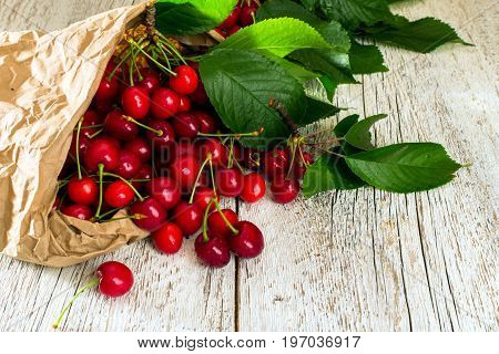 Ripe red cherry with leaves scattered from a paper bag on a white wooden table