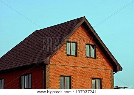 Part of a brick building with a roof and windows