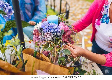 Florist making a flower composition. Wedding details. Woman collecting a composition of different, colorful flowers and a blue candle. Close-up
