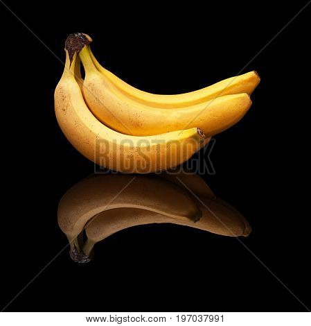 Bunch of ripe bananas with real reflection on a black background isolated