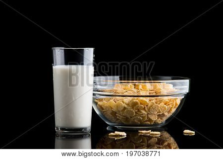 Glass of milk and cornflakes on a black background. Crispy corn flakes for breakfast.
