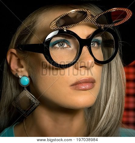 Young blonde woman in stylish sunglasses with a sexy make-up in a turquoise shirt and hat. On a red checkered background