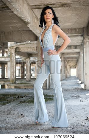 Portrait of beautiful sexy young woman with elegant overall, in urban background. Attractive young brunette with long hair and blue eyes posing fashion in white outfit. Long legs woman, side view