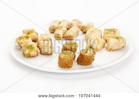 Three Bourma baklava pieces standing out in a plate with assorted cashew and pistachio pastries. Sweet Near Eastern baked dessert with crunchy hair-stick strings twisted around nut filling. Closeup.