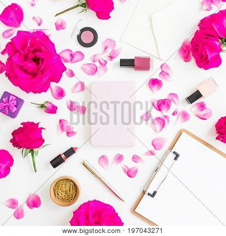 Desk with cosmetics - lipstick, eye shadows, nail polish, pink roses and clipboard, notebook, pen on white background. Flat lay, top view.