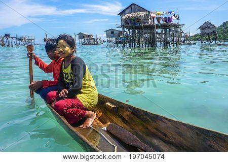 Semporna,Sabah,Malaysia-Apr 23,2017:Sea Gypsy kids on unique handmade boats with clear water on at Bodgaya island,Semporna,Sabah,Malaysia.
