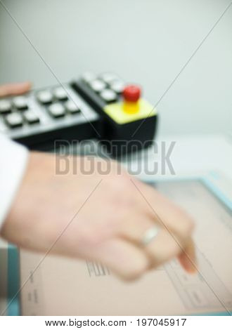 Male hands touching the touchscreen and holding the control panel. Close-up.