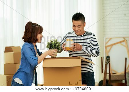 Loving Asian couple chatting animatedly with each other while unpacking cardboard boxes, interior of new spacious apartment on background