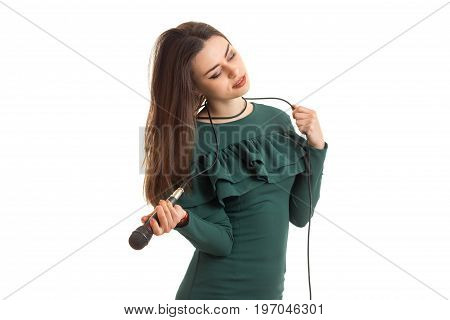Charming lady in green dress with microphone isolated on white background