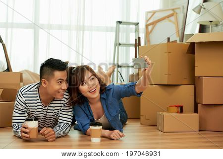 Loving young couple taking selfie on mobile phone while lying on floor and drinking fragrant coffee from paper cups, pile of moving boxes and interior design items on background
