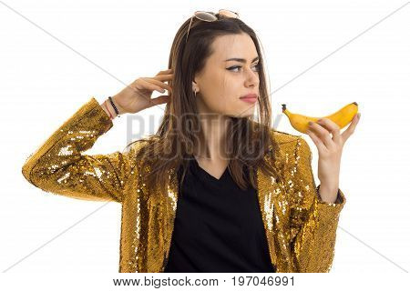 Charming lady in golden jacket with banana in hands isolated on white background