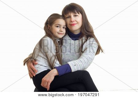 Cheerful adult omther with her little daughter hugs isolated on white background