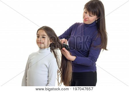 adult mother combs her little daughter hair isolated on white background